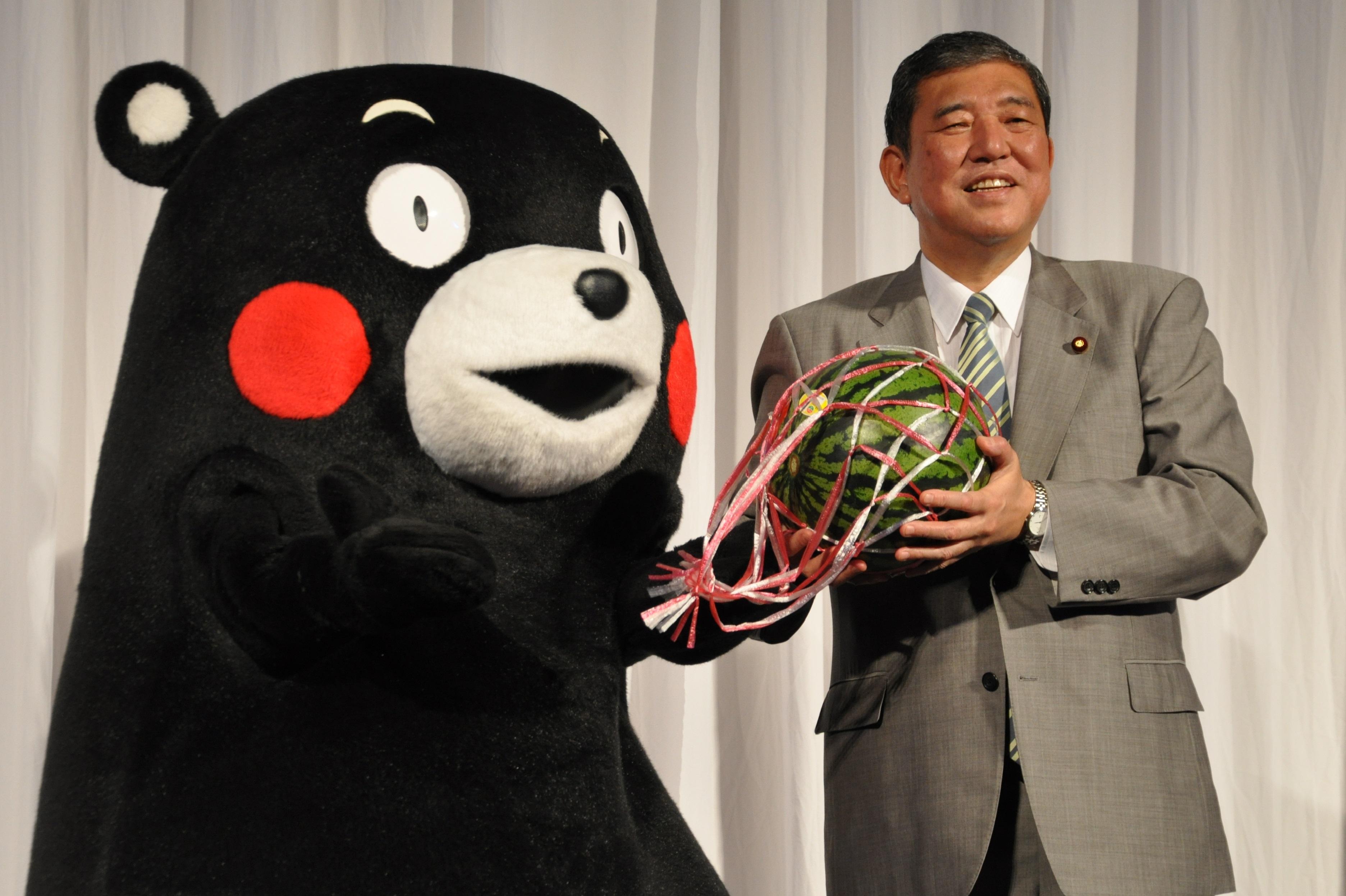 くまモンからスイカを贈られた石破担当相(右)=東京都港区の東京ミッドタウン・ホールで