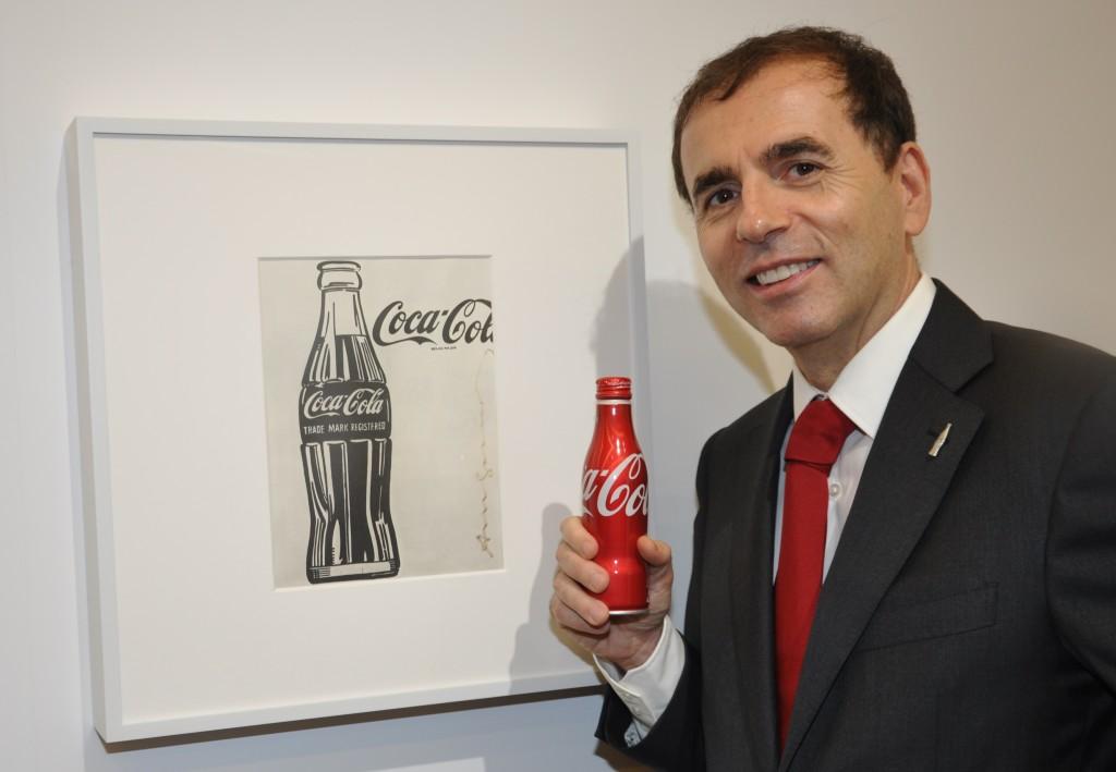 【アンディ・ウォーホルの作品の前で、20日発売の「コカ・コーラ」スリムボトムを持つカリル氏】
