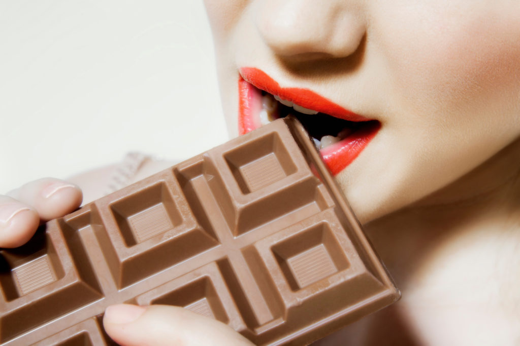 Young woman biting chocolate, close up