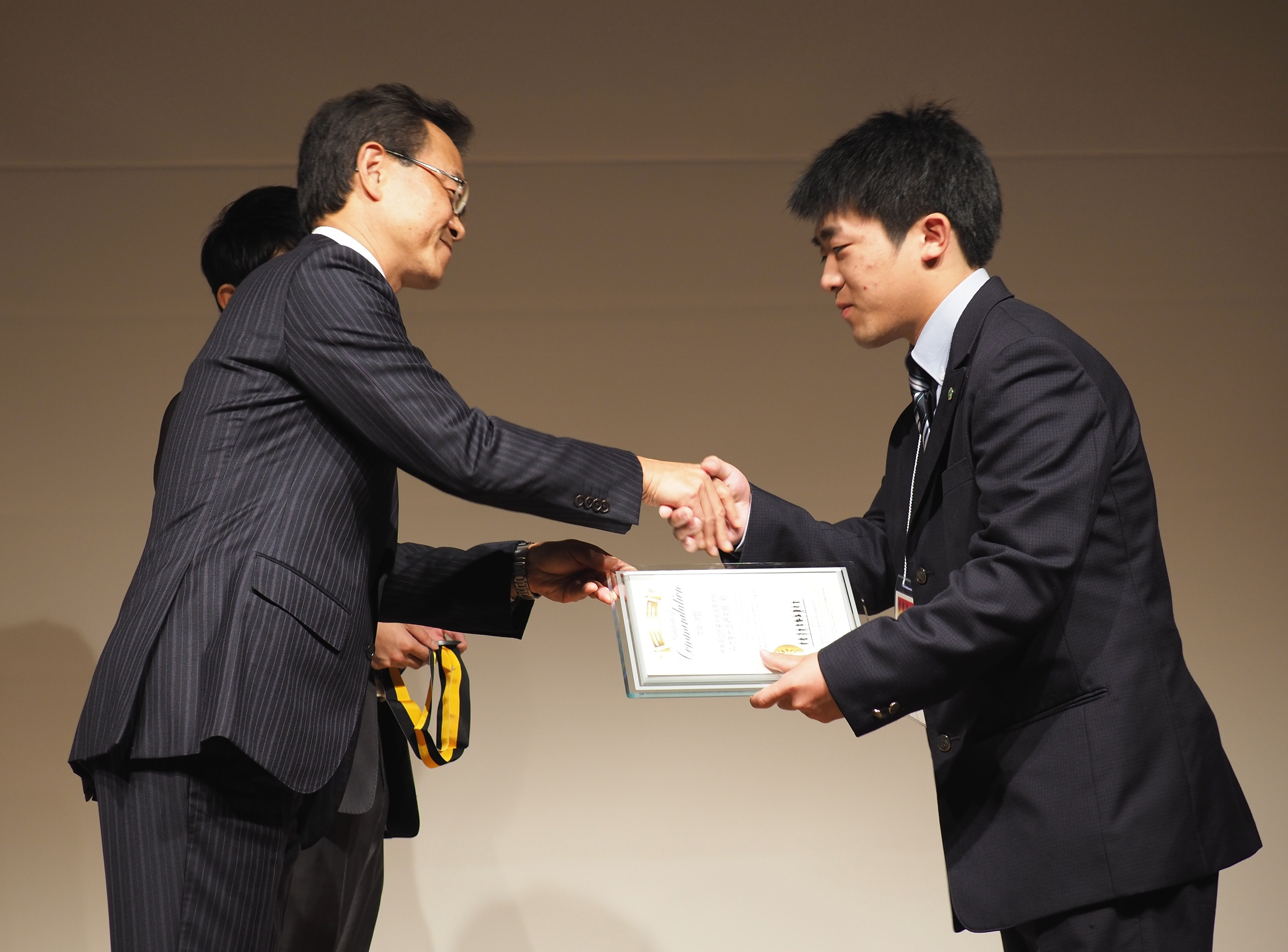 阿蘇中央高みさを大豆研究班の荒牧剛士さんも表彰状を受け取り思わず笑みがこぼれる。
