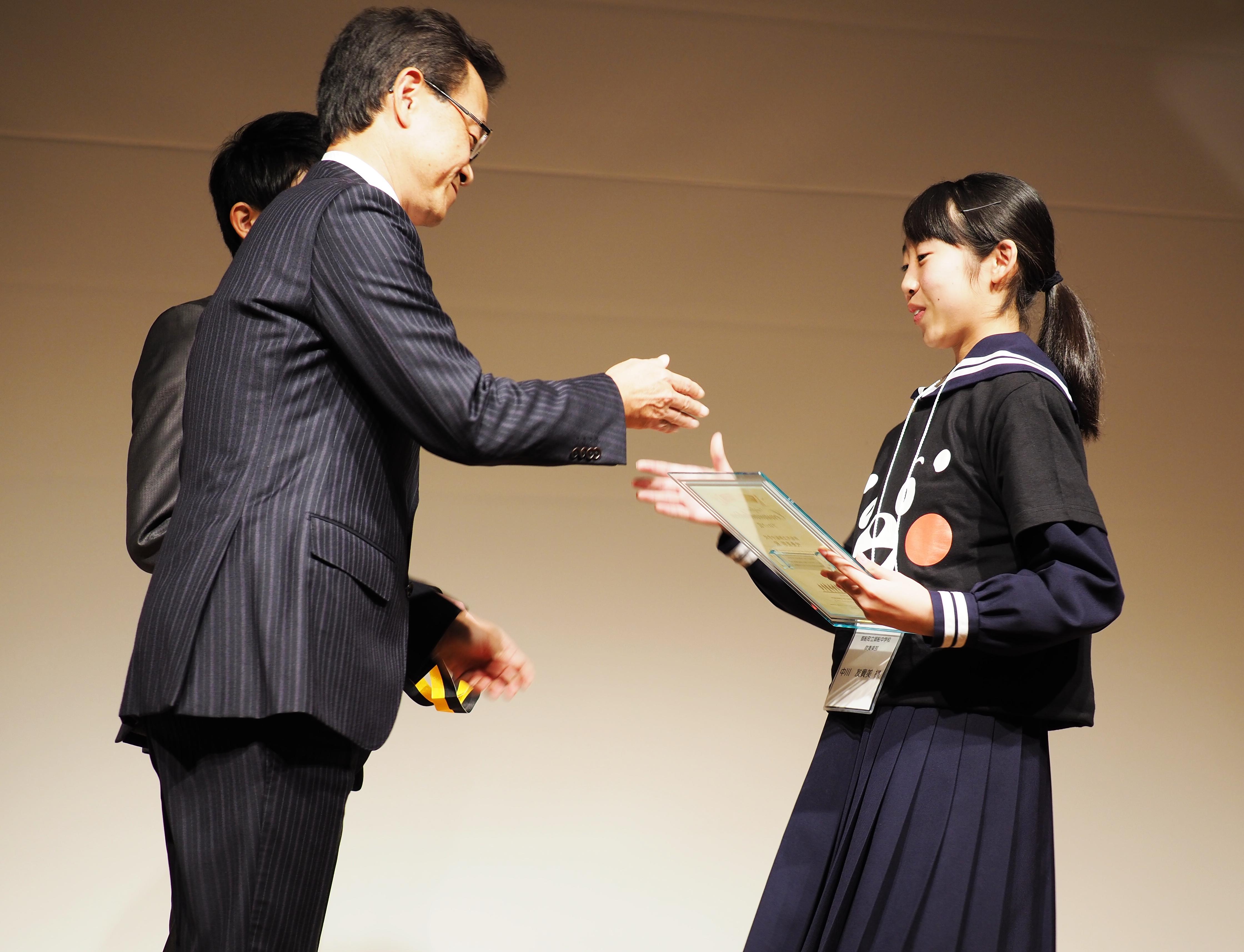 代表して表彰状を受け取る、御船中吹奏楽部の中川友貴美さん。制服の上に着たくまモンのTシャツがかわいい。