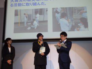 壇上で話す、兵庫県立洲本実業高等学校 ソフトエネルギー研究ユニットのユニットリーダー村上宙君(写真中央)。