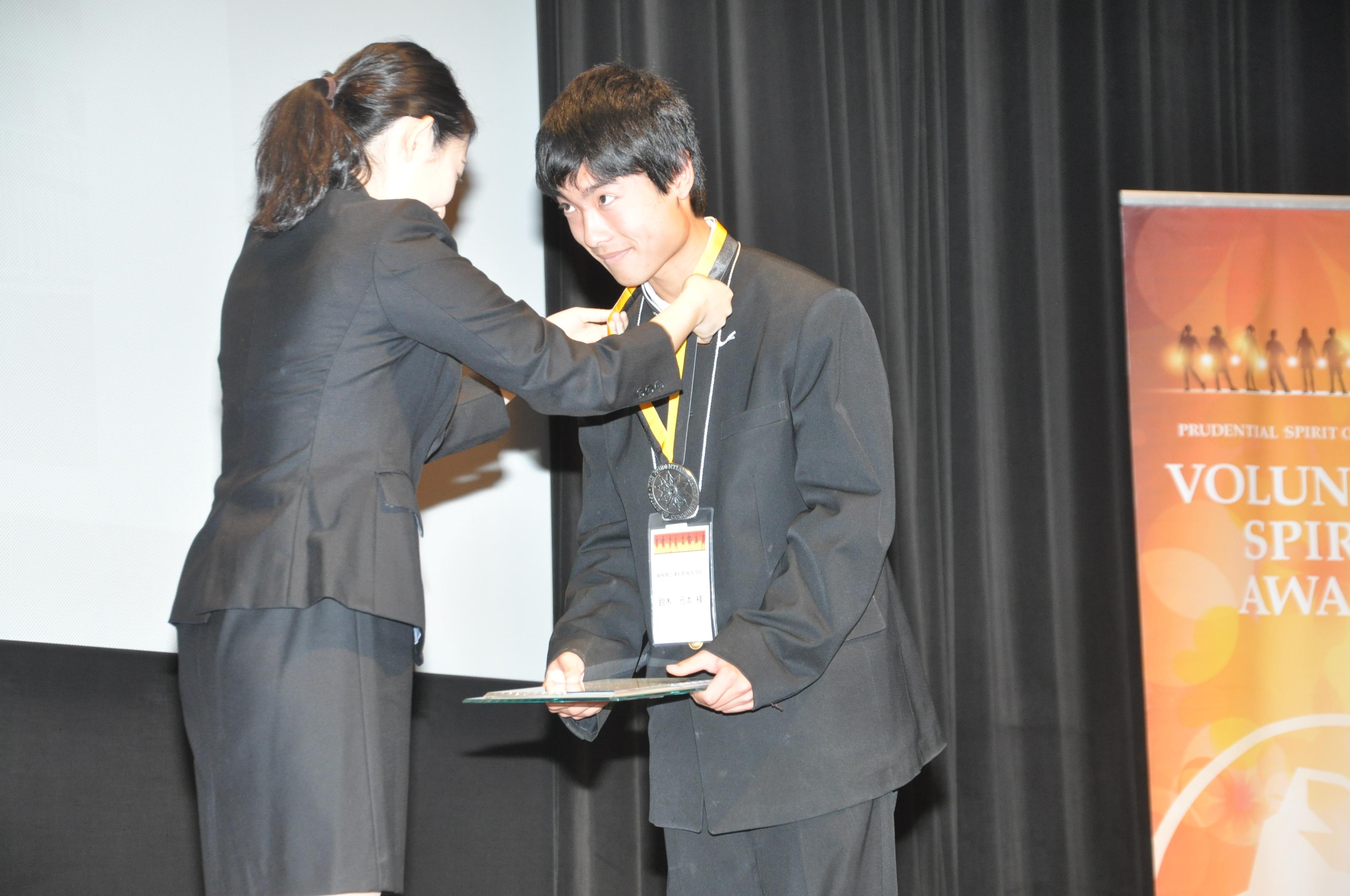 第18回米国ボランティア親善大使の櫛部紗永さんから、受賞メダルを首に掛けてもらう鈴木さん(右)。