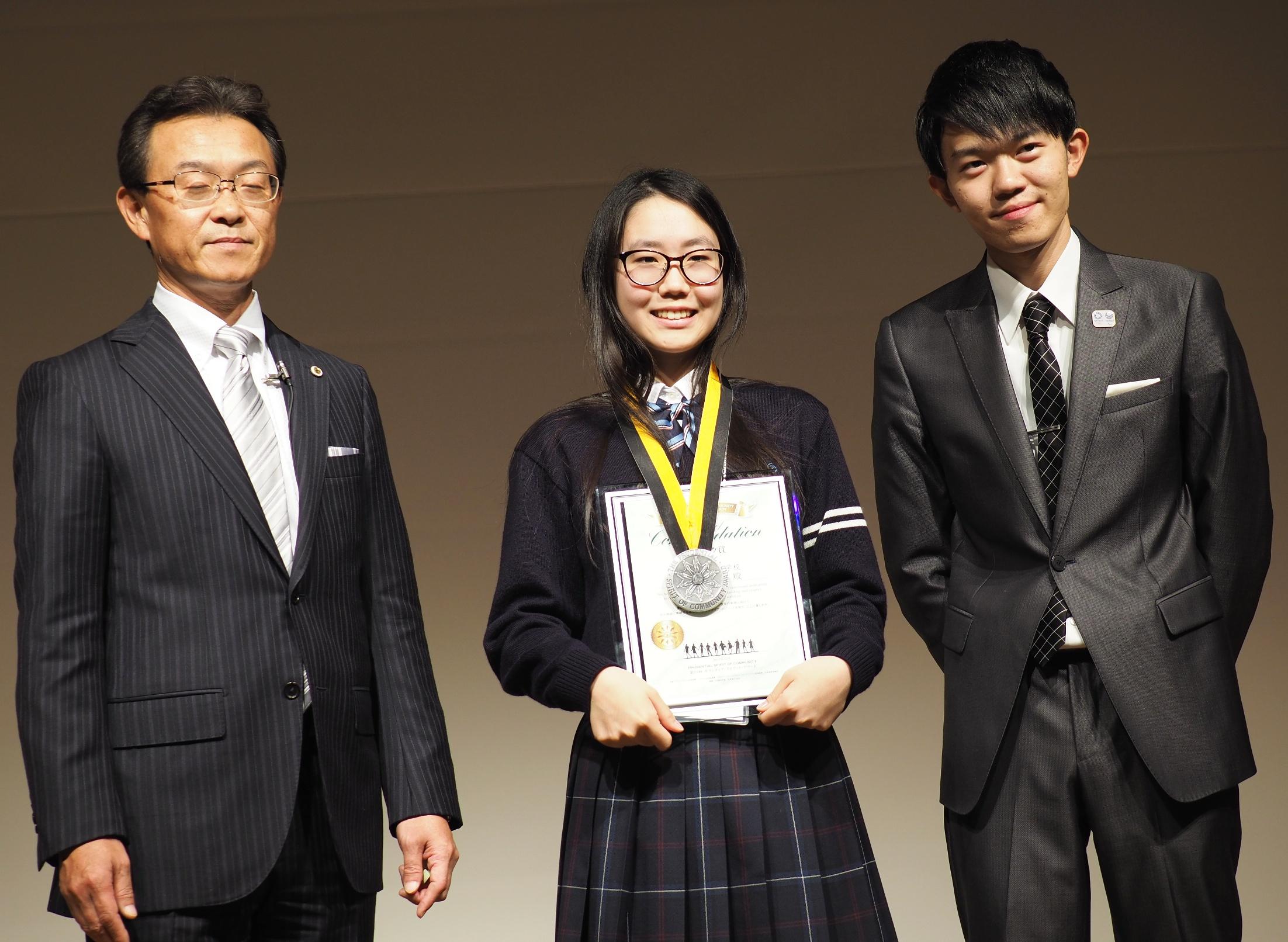 語学を教える難波沙和さん(写真中央)は自身も来年留学の予定だ。今回、メダルのプレゼンターとして受賞者OBで米国ボランティア親善大使にも選ばれた森野宇宙(もりの・たかとき)さん(写真右)も参加し、スピーチも行った。