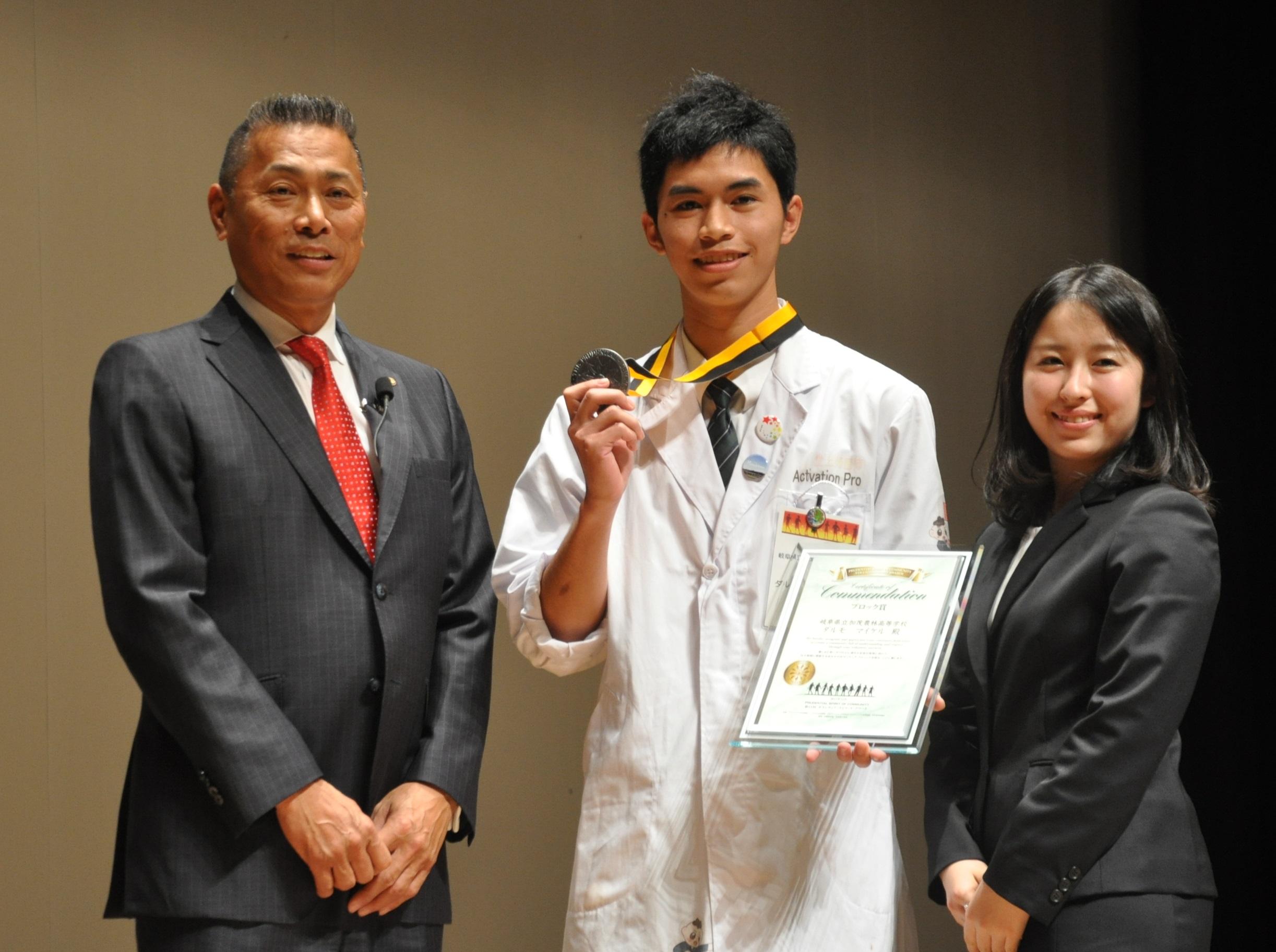 メダルを手に笑顔のダルモ・マイケルさん(写真中央)。