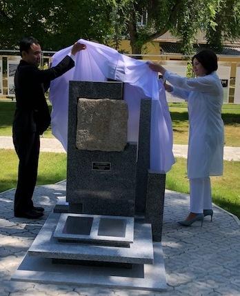 「祈りの石」を除幕、披露する梅本道生ひろしま・祈りの石の会会長とモルドバ共和国のモニカ・バブク教育・文化・研究相。