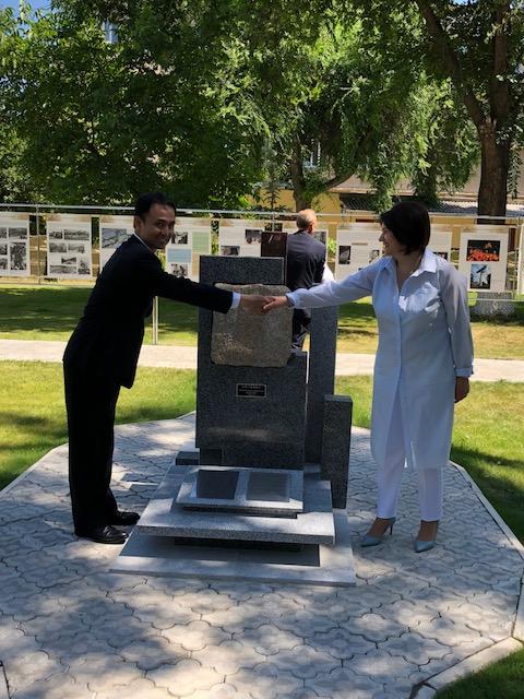 梅本道生ひろしま・祈りの石の会会長(左)と握手するモルドバ共和国のモニカ・バブク教育・文化・研究相(中央は「祈りの石」)。