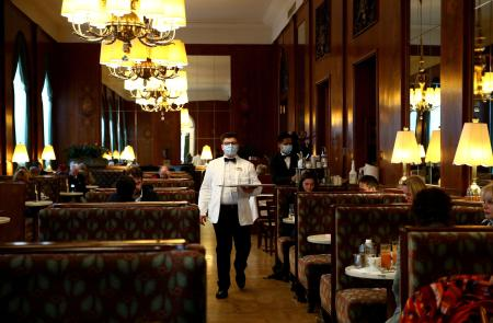 カフェで接客するウエーター=15日、ウィーン(ロイター=共同)