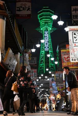 大阪府の休業要請などを段階的に解除する基準「大阪モデル」の達成状況を表す、緑色にライトアップされた通天閣。大阪・新世界では営業再開した飲食店もあり、人通りが増えてきた=22日夜