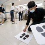 食料品売り場の営業再開を控え、床に貼られる並び位置を示すマーク=24日午後、東京都中央区の百貨店松屋銀座
