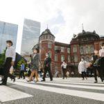 マスク姿で通勤する人たち=25日午前、JR東京駅前