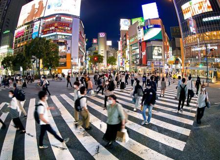 安倍首相が緊急事態宣言全面解除を表明した25日夜、東京・渋谷のスクランブル交差点を行き交う人たち(魚眼レンズ使用)