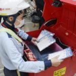 政府が全世帯へ配布する布マスクを配達用のバイクに積み込む郵便局員=14日、名古屋・西郵便局