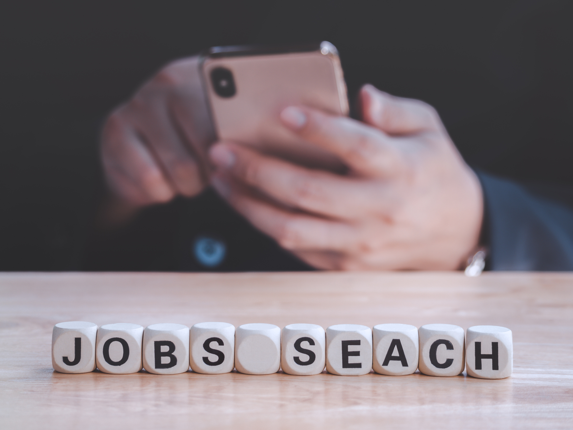 Closeup wooden block written Jobs Search on table against bussinessman using smart phone to find new jobs and application. Employment concept.