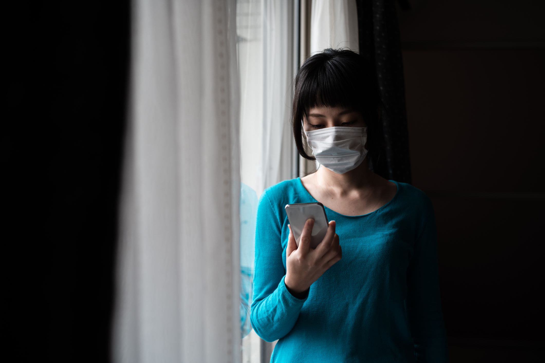Indoor portrait of Asian woman wearing surgical mask operating smartphone at the window