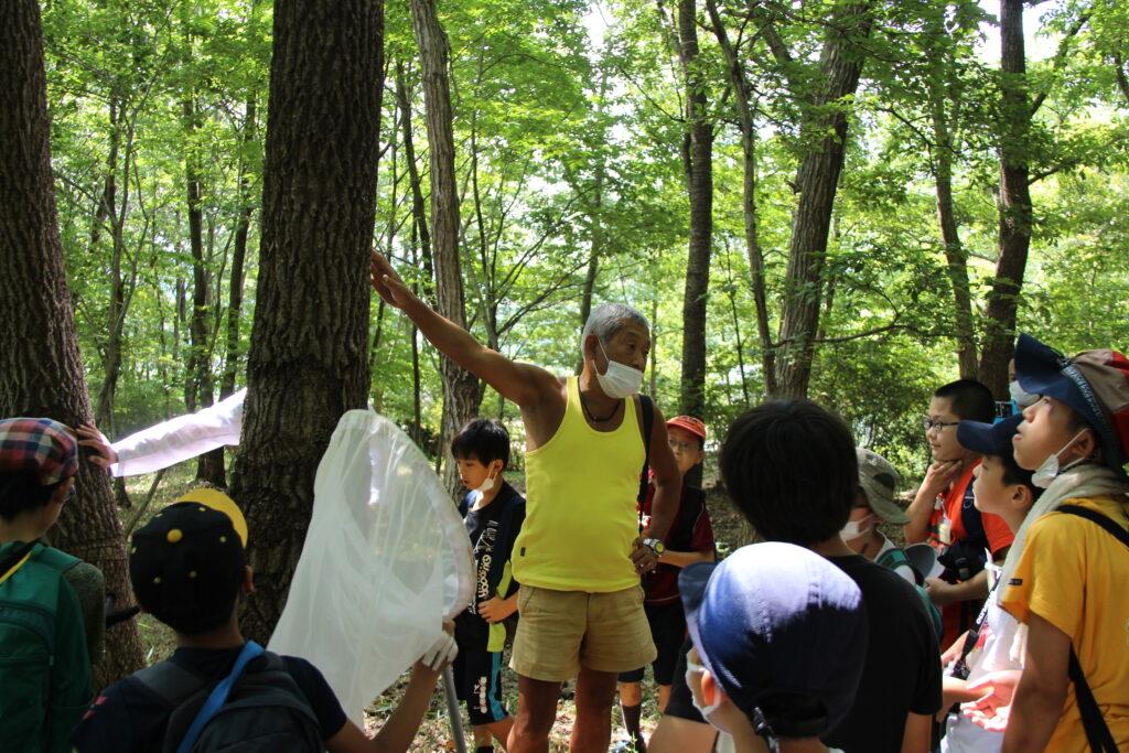 森を案内する崎野さん。