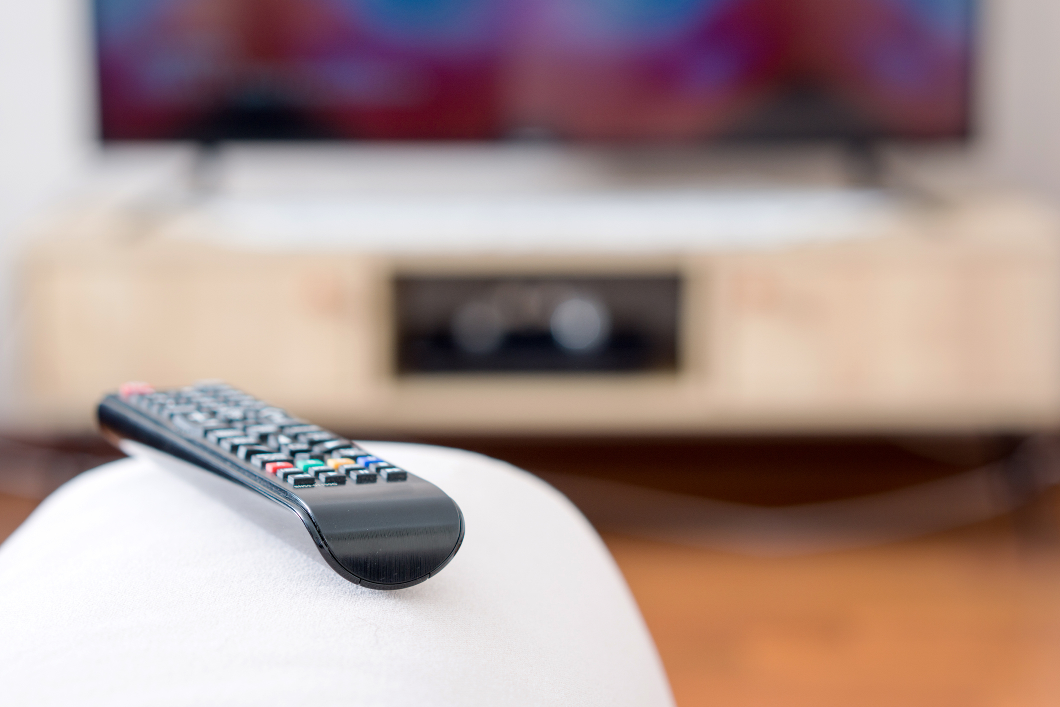 One TV remote control on the armrest of sofa