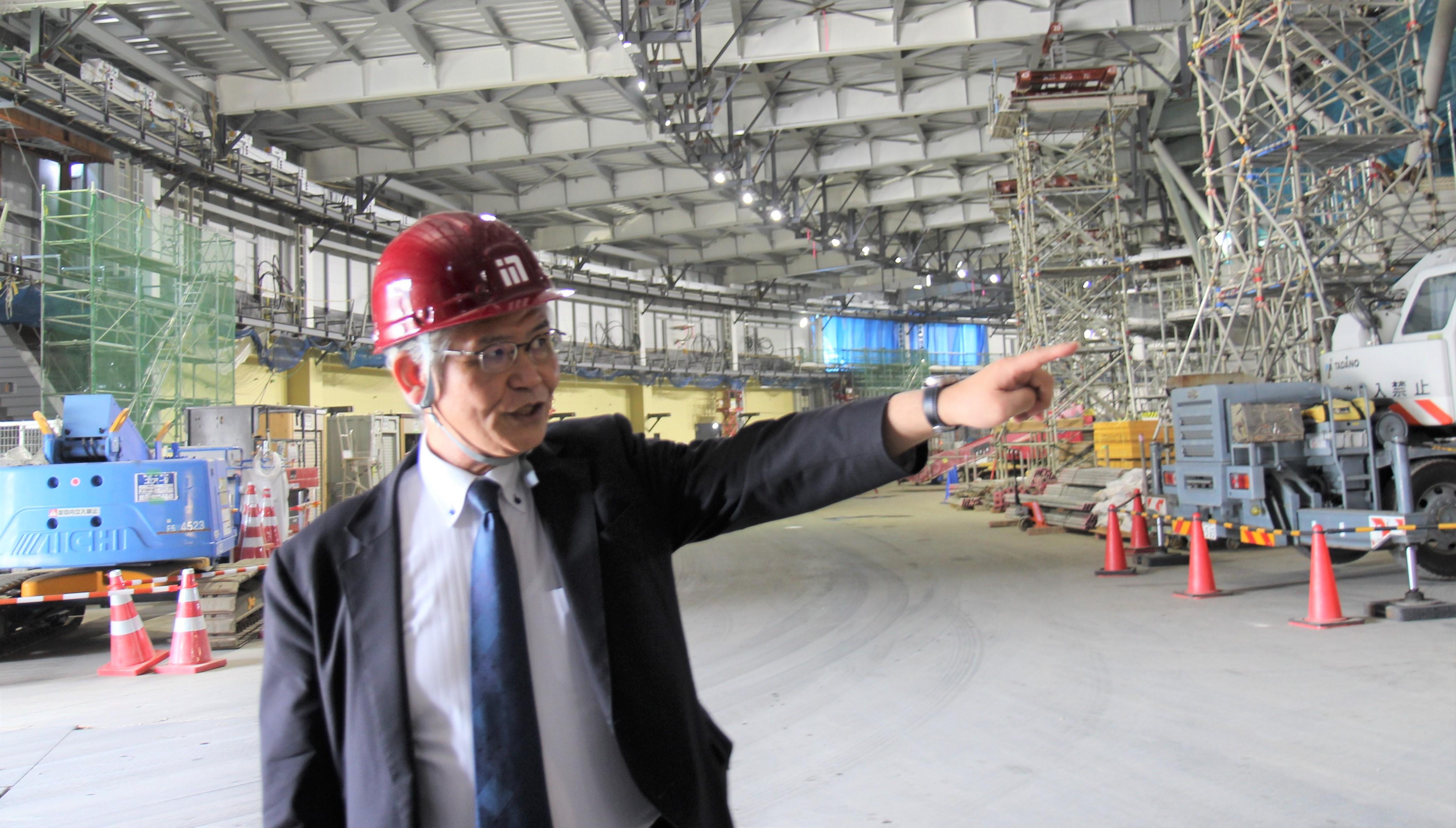蓄積リングが設置される建屋で説明する高田昌樹理事長。
