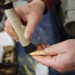 根付は、彫り上がった後の磨きも重要な作業。1カ月かけて彫ったものは1カ月かけて磨きなさいと言われるとか(写真の手は梶浦さんではありません)。磨いた後は、木の実を煮詰めた液で着色して完成する。